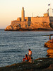 A family takes in the sunset from the breakers on the Malecon in Havana, Cuba (Castillo del Morro is in the background).