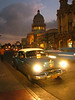 Hitchhikers jump into a classic 1950s car with the former National Capitol building in the background in Havana, Cuba.