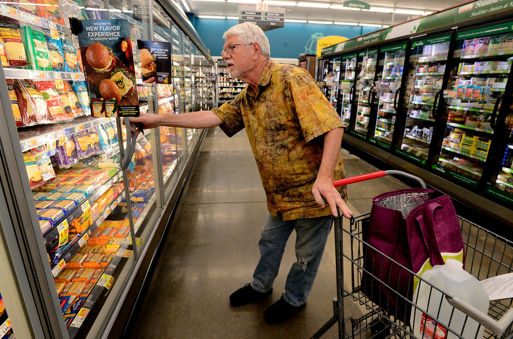 . Matt Reynolds, a volunteer with Cultivate, shops in the frozen food case for a homebound senior at the King Soopers on Table Mesa Drive in Boulder  on Thursday. For more photos go to dailycamera.com Paul Aiken / Staff Photographer / May 17, 2018