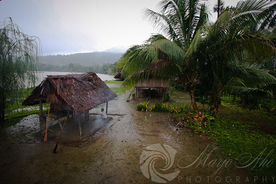 It is a rainy day. The houses are built on stilts as the river will rise during the rainy season.