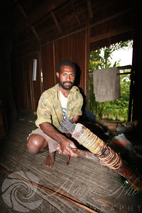 George holding a sago axe which is used to carving the sago pulp out of the sago palm trunk.
