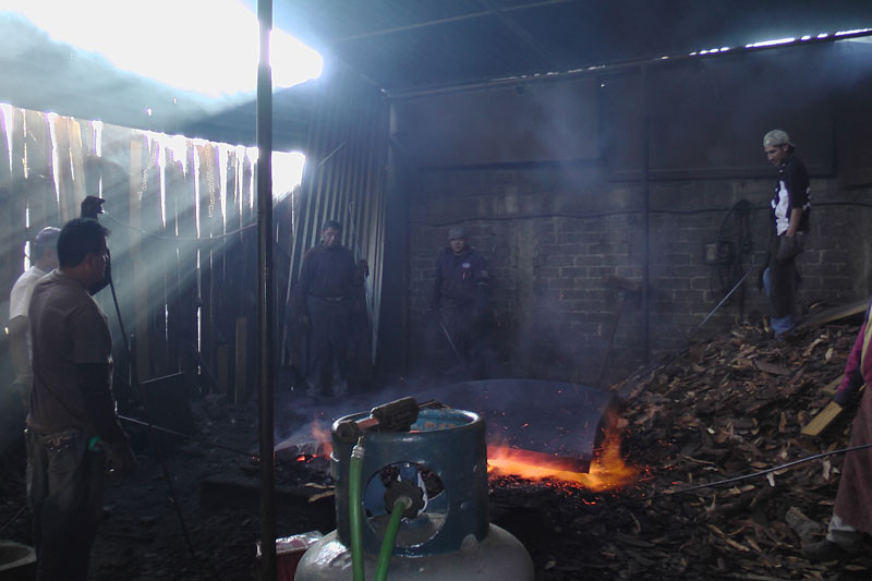 This photo and the following four photos so the fire process to bring out the patina colors. It took six men to handle the copper lamina in the fire because of the size.