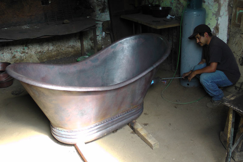 This photo was taken in the workshop. They are just starting to burn the dark brown patina onto the formed tub.