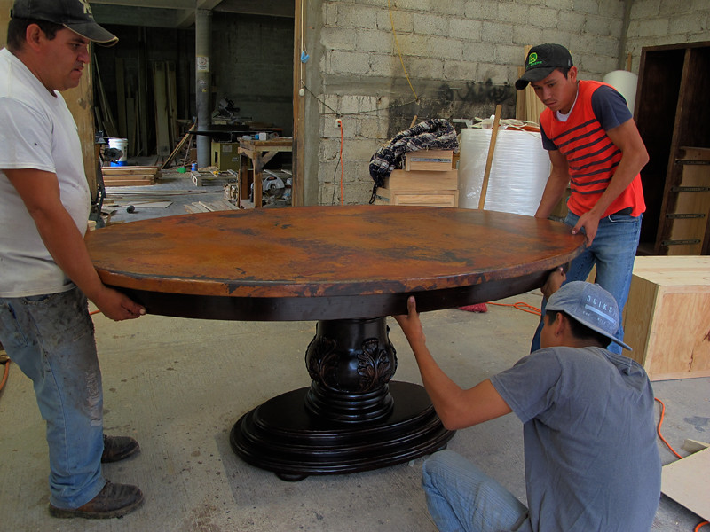 Three men work together to place the table top on the table base.