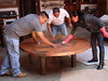 The table top has just been brought from the workshop into the showroom where they are applying the protective wax coat. The wax coat also accentuates the colors in the patina.
