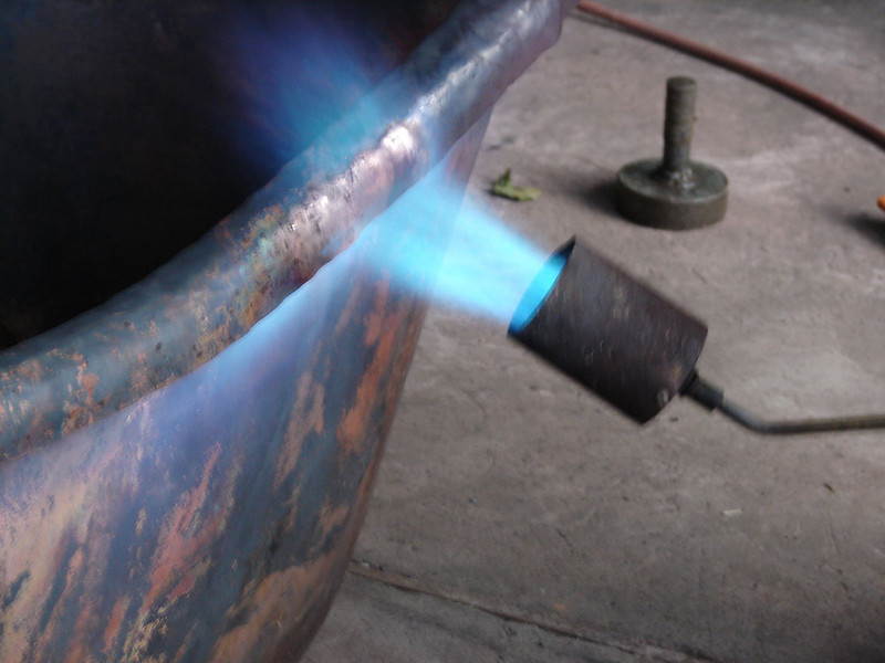 (11) Curving the lip. First, fire; then hammering.