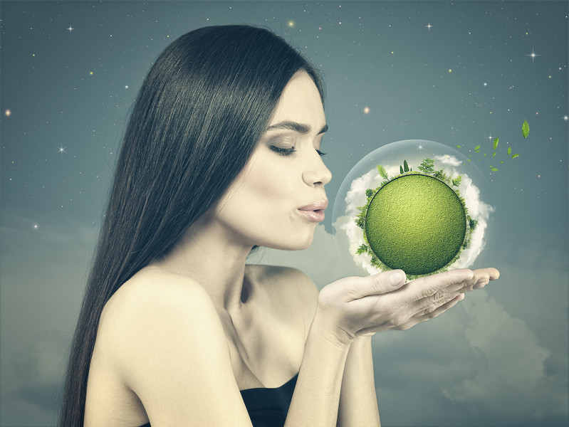 Eco female portrait with beauty white girl holding green planet on to his palm