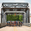 """Joe Martin Stage Race. Stage 2. UCI Pro 1 Men. The field is rolling across a steel girder bridge in the Arkansas countryside while a breakaway is working hard establishing a lead which will eventually swell up to 5' 55""""."""