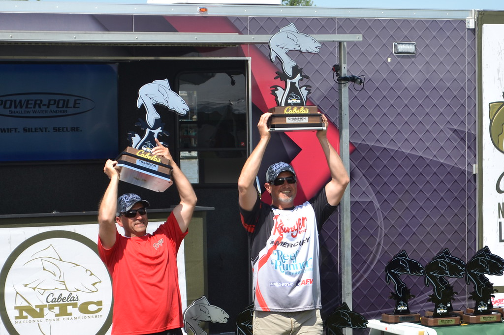 . Keith Reynolds � The Morning Journal <br> Erick Williams, of Hubbard, left, and Sammy Cappelli, of Poland, hoist trophies they received for their win at the Cabela�s National Team Championship walleye tournament June 10 at Black River Landing in Lorain.