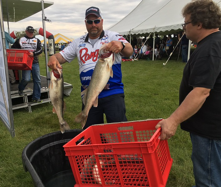 Richard Payerchin — The Morning Journal <br> Buck Gehm of Crivitz, Wis., center, gets ready to set two of his team's walleye in the carry basket after taking photos at the Cabela's National Team Championship walleye tournament in Lorain on June 9, 2017.