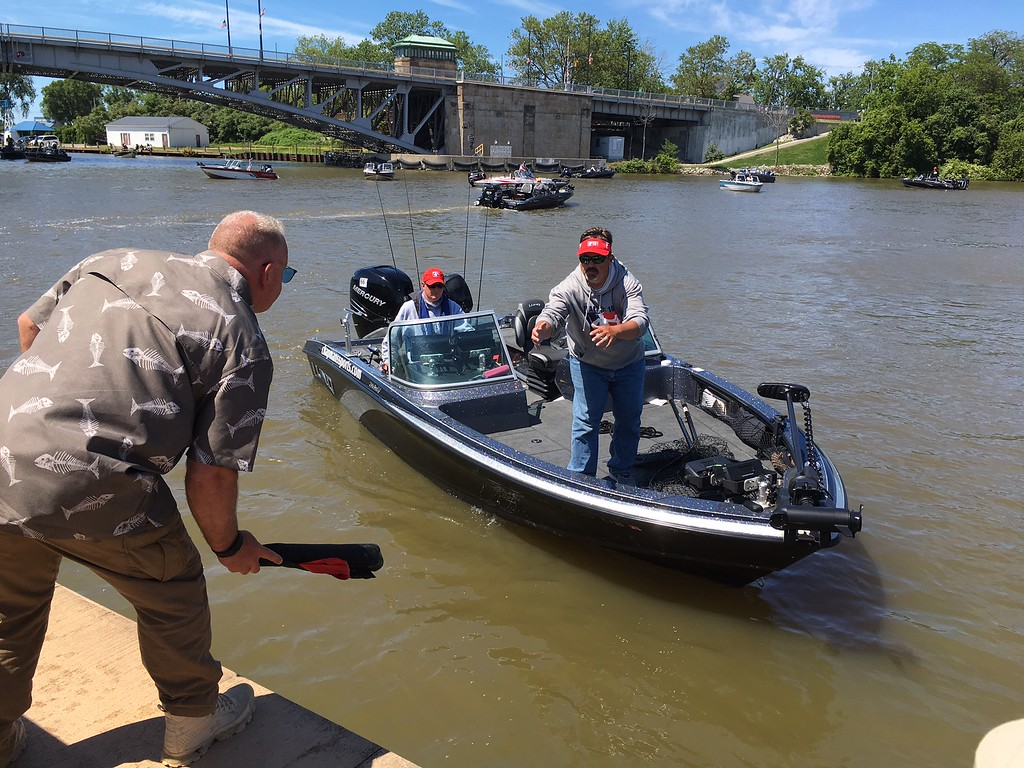 . Richard Payerchin � The Morning Journal <br> Lorain Port Authority Executive Director Tom Brown gets ready to toss over a fish bag to one of the teams in the Cabela\'s National Team Championship walleye tournament at Black River Landing in Lorain. The three-day contest started June 8, 2017, continues June 9 and 10.