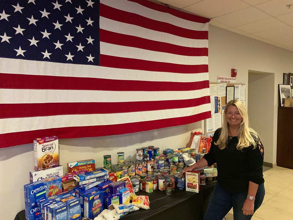 . Elks Chairwoman Mindy Westberry of Westford proudly shows off all the food collected.