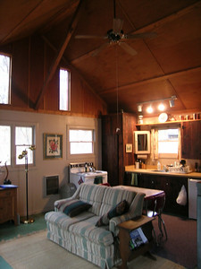 The living room area, kitchen in background