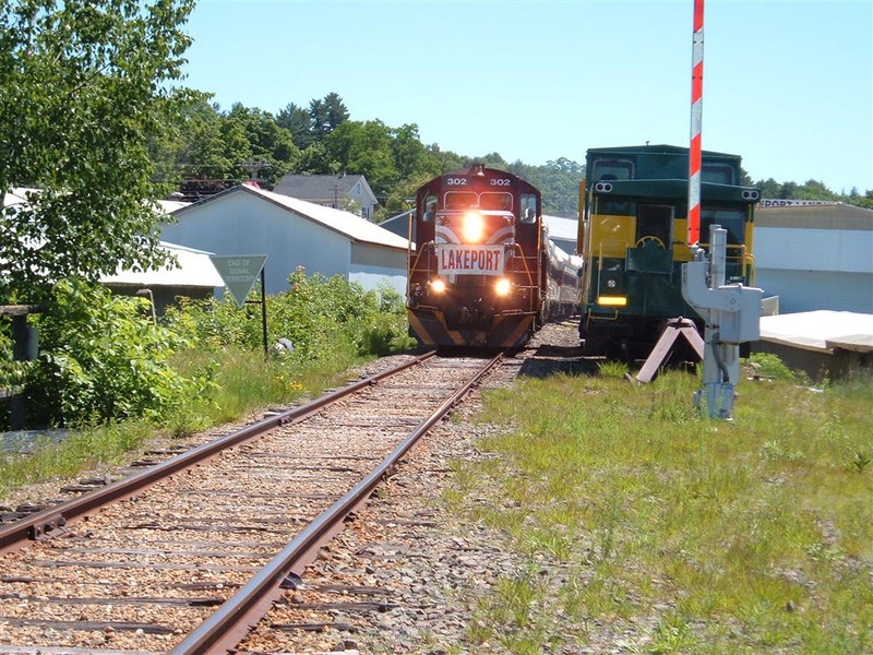 Engine 302 leads the 1pm local to Weirs Beach with a large crowd destine for Motorcycle Week festivities. Here it passes Caboose 51 on the siding just south of the Lakeport Drawbridge.