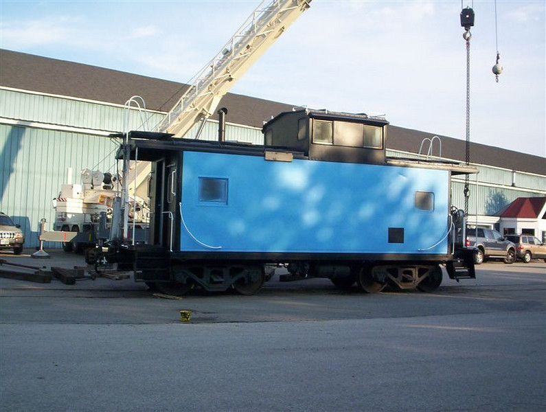 <strong>On Its Trucks:</strong>  Caboose Is lifted onto its trucks  Photo by  George Kenson