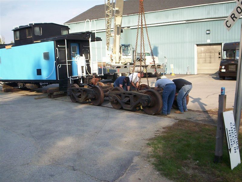 <strong>Trucks are planted on the tracks:</strong>  The caboose's trucks are carefully set on the tracks as Troy holds his breath. George Kenson Photo