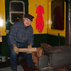 <strong>Caboose Conductor Ben Perry</strong> Caboose Conductor Ben Perry puts another log on the fire as temps were in the teens as we head north Sunday Dec3rd to Lincoln. The wood stove gave more than enough heat allowing us to open the cupola windows and doors.