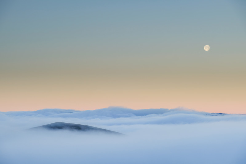 Moonset over a cloud-filled strath