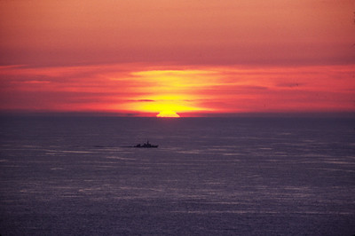 An unidentified warship sailing past the sunset. Pentland Firth.