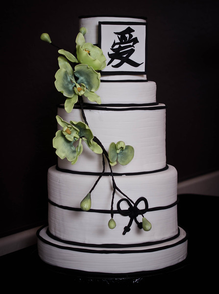 "Asian-inspired 5-tier cake. This design was my own creation, start-to-finish. The placard displays the Japanese symbol for love, done in 3D ""brush strokes."" The beauty of this design is that the orchids take center stage and can be done in various colors."