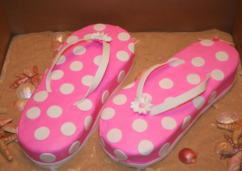 Flip flops - two yellow cakes covers with buttercream.  Fondant dots.  Gumpaste thong. Royal icing flower.  White chocolate shells and star fish.  Brown sugar sand.  Feeds 10-12 $75.00