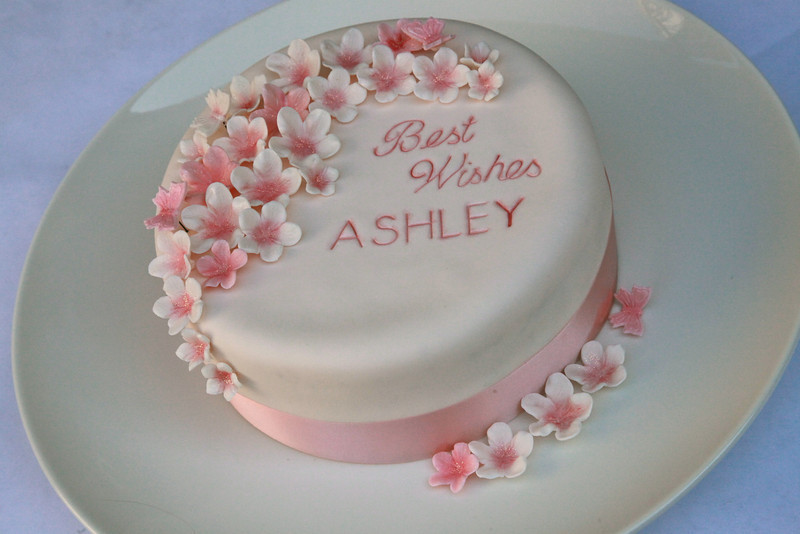 Gluten free, fondant covered cake with sugar flowers and butterflies, and lettering embossed onto cake.