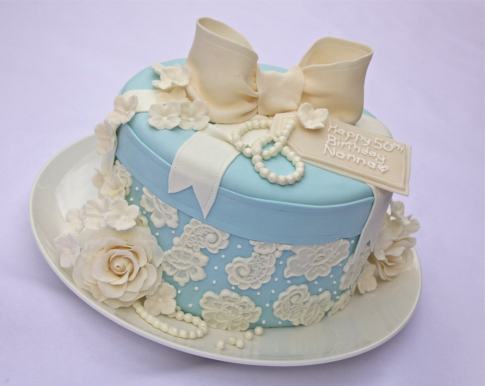 "10"" Vanilla with extra tall layer - Wedgewood blue hat box cake for a milestone birthday party. With hand made gum paste bow, tag, roses and hydrangea flowers. Fondant lace and pearls also hand made. Entire cake was made from scratch, with no additives or preservatives (as always) :)"