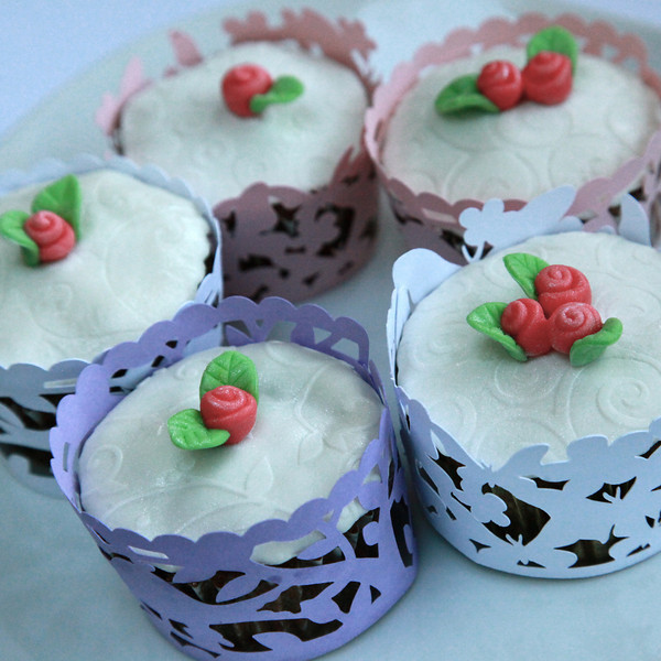 Carrot cake cupcakes with embossed fondant icing on top, and tiny fondant roses. Many styles of cupcake wrappers available