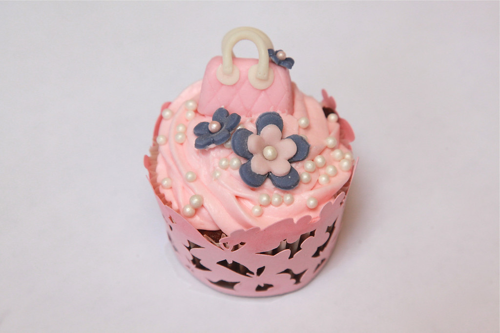 Homemade fondant icing purses and flowers, with white sugar bead sprinkles, on pink cream cheese icing, on carrot cake cupcake. All from scratch, all natural. Cupcake wrappers in many styles available.