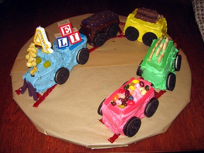Eli's Train Cake, by Craig (12/7/08). (Click here for more photos) The engine has a Twizzlers cattle guard, DOTS gum drop headlights, Pirate's Booty puffed corn steam, and alphabet block cargo.  The coal car features Nestle Toll House Mini Morsels miniature chocolate chip coal.  The yellow lumber car is carrying Nestle Stixx logs.  The green circus car is carrying animal crackers.  The caboose is topped with jelly beans.  Each car has Twizzlers rails, Oreo wheels and sits on Twizzlers tracks.