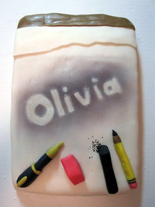 Olivia's Drawing Cake, by Craig and David (6/28/10) (Click here for more photos) Everything seen here is edible, and everything is made entirely from fondant with the exception of the edible black color mist used around the letters, the silver dust on the letters, and the black sprinkles for the charcoal shavings.  The pink erasers and gold elements of the fountain pen are custom-blended colors.