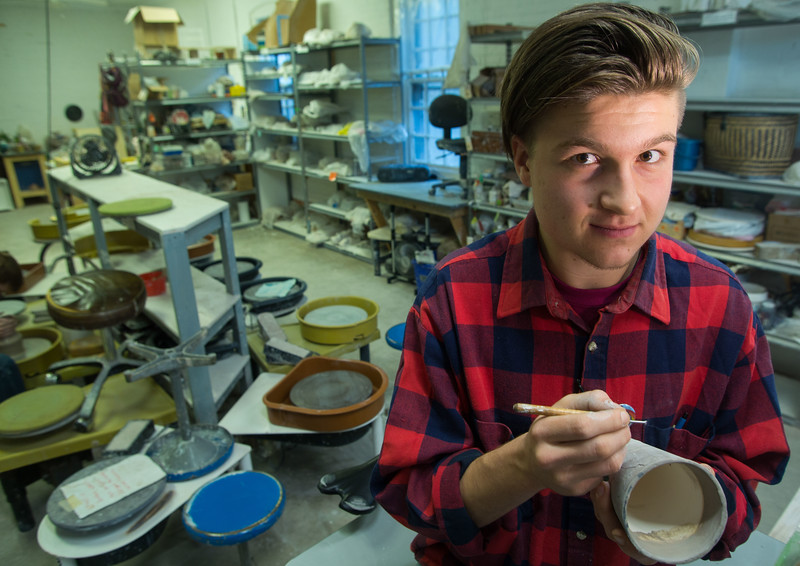 "October 16, 2016. ""Pottery is a hobby for me,"" Marval Rex says, ""I get to meet and help so many different people who want to make their own work of art.""<br /> Marval Rex (cq), a potter at Flower City Pottery, in Rochester, N.Y. draws a design on his clay cup before firing."