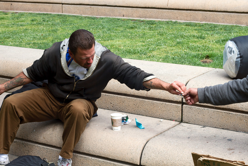 Some homeless-looking guys passing a 'non-tobacco' cigarette in Union Square, SF