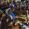 Photo by Walt Hester<br /> Elite-Pro men stride over a barrier and head up a steep hill. Cyclocross is a hybrid of road cycling and cross-coutry running, originally created to keep European road cyclists in shape through winter. Now 'Cross racing is a specialty all its own.