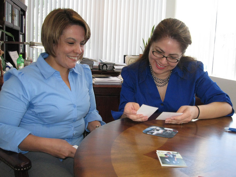 Rosa Teresa Gutierrez, left, shows photos of her children to Carmen Chavez, executive director of Casa Cornelia Law Center. Rosa, a native of Guadalajara, Mexico, received free legal aid from Casa Cornelia when her husband was physically, mentally and sexually abusing her. Casa Cornelia is a public service law firm providing pro bono legal services to victims of human and civil rights violations.