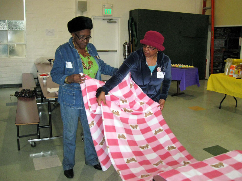 Darlene Love, SWO board member, left, and Janice De Mar, both of Olivet Lutheran Church, Hawthorne, roll up material for blankets.