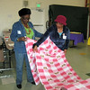 Darlene Love, SWO board member, left, and Janice De Mar, both of Olivet Lutheran Church, Hawthorne, roll up material for blankets.