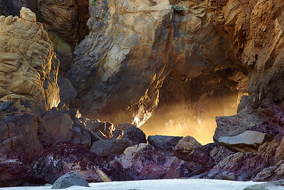 A sea cave near the main portal on this beach is also a great source of light during the winter at sunset.  The sandstone and Tafoni rock formations have been sculpted into twisted formations while the waves have done their work to bore holes into the soft rock.  It is as though the light was boring the hole on this evening as the sea mist drifted into the cave.