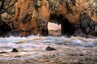 This opening in a cliff face at Pfeiffer Beach in Big Sur allows large waves to come through at high tide before a big storm. The waves often fill the entire portal to the top, and the portal becomes a giant water shotgun!  The Tufoni formations in the rock are incredible and should be seen in person.  The sun was only like this for about 30 seconds so I had to work fast.  Fortunately, the sun was dimmed by high clouds but there was still enough light to reflect onto the rock face from the cliff behind the camera.  Backlighting is crucial here; otherwise you have an overexposed portal with no detail on the rock face.  Once the light was right, I waited for the water flow to become dramatic.  A short exposure time allowed a little movement while retaining detail of the sea spray.