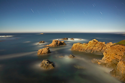 There was a full moon rising in the darkness over Soberanes Point in Garrapata State Park in Big Sur. I could see the moonlight on the water and how it cast shadows across the small islands of rock. This long exposure shows the stars in motion with the sky appearing nearly as though it was daytime. The fog in the distance moved onshore shortly after I was finished, so I was fortunate to capture this scene.   Even though it was  nighttime, my eyes became accustomed to the low light and I was able to see the deep blue color of the sea.  The shimmering waves took on mystical properties as I sat alone on the rocky outcrop where I had placed my tripod listening to the waves and the coyotes.  It was the mystical atmosphere that I hoped to capture on this night.