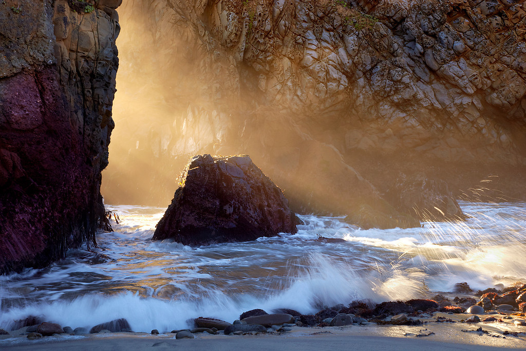 Sea mist and light streamed through an opening between two Tafoni sandstone sea cliffs at Pfeiffer State Beach, in Big Sur, California.  This light does not last for long!