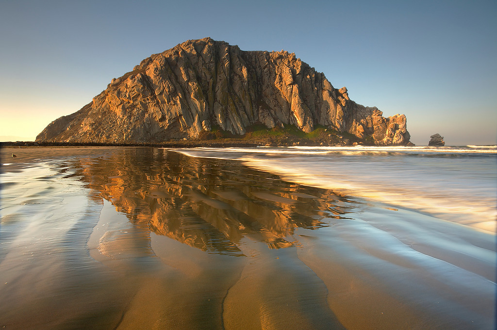 Morro Rock, is the 576 ft. tall plug of an extinct volcano and is one of a series extending for many miles inland. In the winter, the sun cuts across the rock face at sunrise and illuminates the rock and sand ripples perfectly.  This low sun angle is the only way to show fine detail in the sand.  It only lasts for about 3 minutes, so I had to work fast.  A low tide also exposed just enough sand while keeping it wet for the best effect.  I liked how the sand ripples pointed in the same direction as the layers of rock.