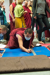 Starting work on the sand mandala: the monks drew an exact scale replica of the sacred artwork on a large blue surface.