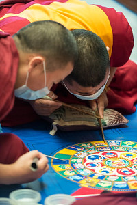 A slow process: tap, tap, tapping the tube to release a few grains of sand at a time. The monks wore masks so their breathing wouldn't disrupt the sand.