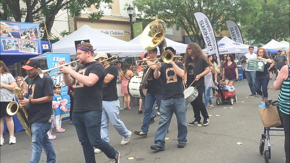CINTIA LOPEZ - DAILY DEMOCRAT The City of Trees Brass Band walks down Main as they play a song after their set at Heritage Plaza.