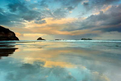 Trinidad State beach is a photographer's paradise, especially at low tide.  The flat beach creates lots of pools and reflective sand patterns.  Here, the first light of day brightens up the higher clouds, leaving the lower ones still in the shadows for extra drama on a warm and humid morning.