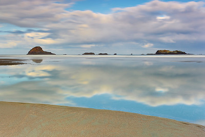 A very low tide on this morning created a still pool that extended out to the breakers.  Every minute or so, waves would interrupt the stillness and then things would become still again.  I waited for a time where I would get 30 seconds of stillness.  The extra long exposure made things look even more still, and was made possible by a very dark circular filter.  The clouds moved a lot during the 30 seconds.  I made sure to include some solid sand and some offshore rocks and islands to anchor the image somewhat to reality!