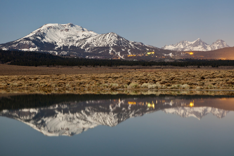 Mammoth Mountain illuminated by a full moon and casting a reflection on a unnamed pond