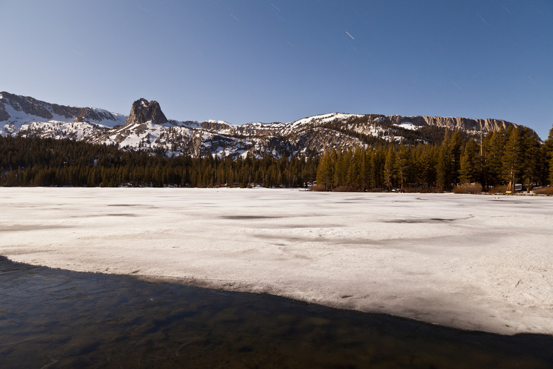 Lake Mary covered with ice in Mammoth illuminated by a full moon. Crystal Crag and the Mammoth Crest in the background.
