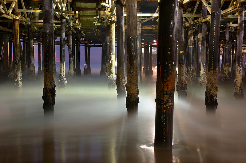 It was like another world under the pier at sunset. The lights allowed extra detail to be seen on the vertical pilings, while a long exposure softened the water.  It took a while to get the best vantage point where the fewest pillars were blocking other pillars while still showing glimpses of the ocean beyond.  And I had to avoid the bright lights, which would become seriously overexposed and ruin the image.